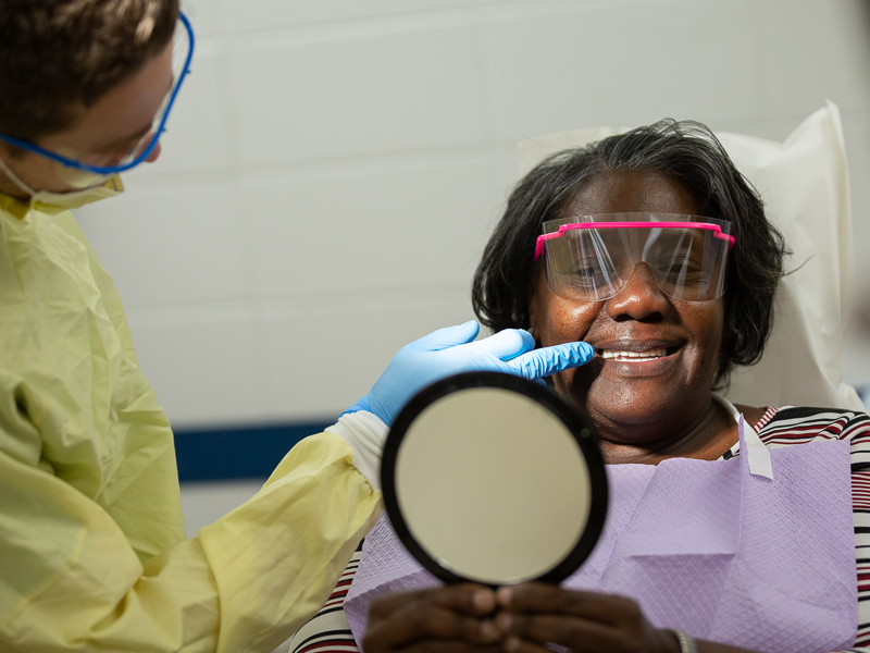 Patricia Hubbard, who was one of 22 patients to receive a free set of dentures during Dental Mission Week, checks out her new smile.