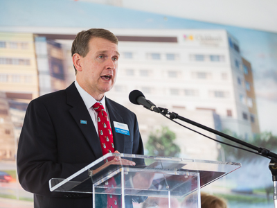Guy Giesecke behind clear podium speaking at ground-breaking ceremony for pediatric expansion.