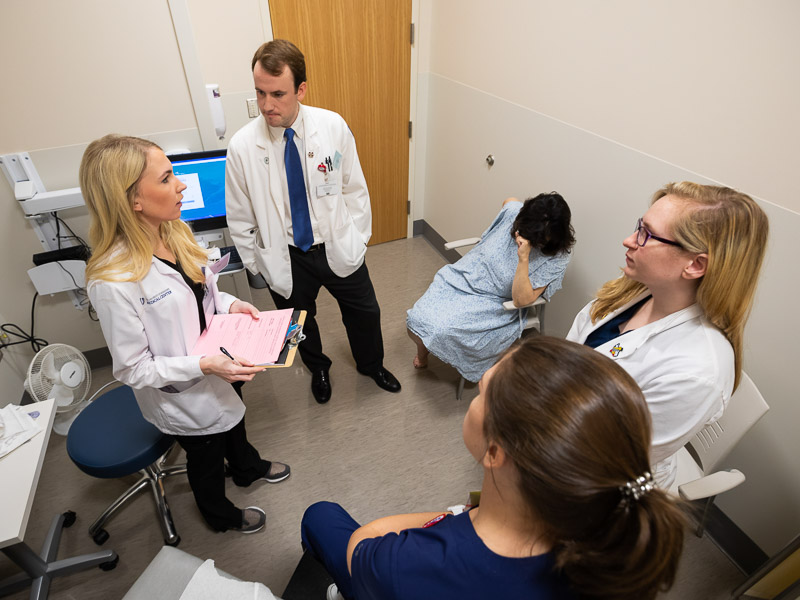With Standardized Patient Dr. Brenda Sumrall Smith, background, seated, are, clockwise from left: Emily McDermott, Ben Matthews, Alyssa Reid and Madison Quinn.
