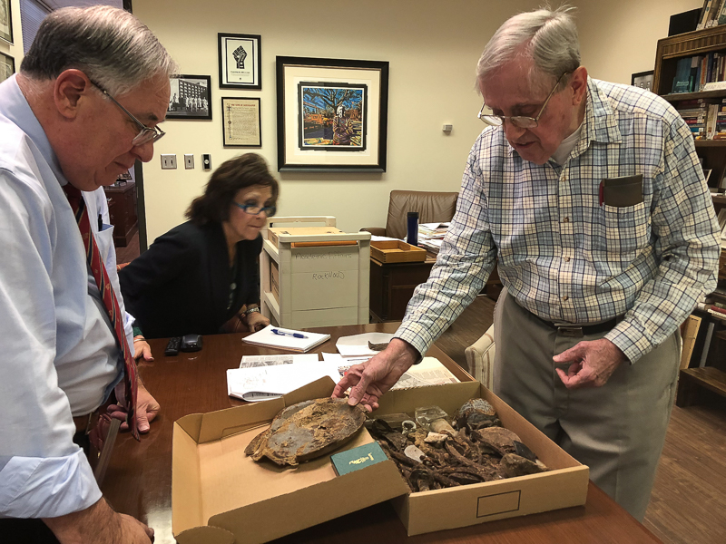 David Juergens, right, unpacks a box of his collected artifacts for Dr. Ralph Didlake, chief academic officer, and Pamela Steadman, executive assistant.