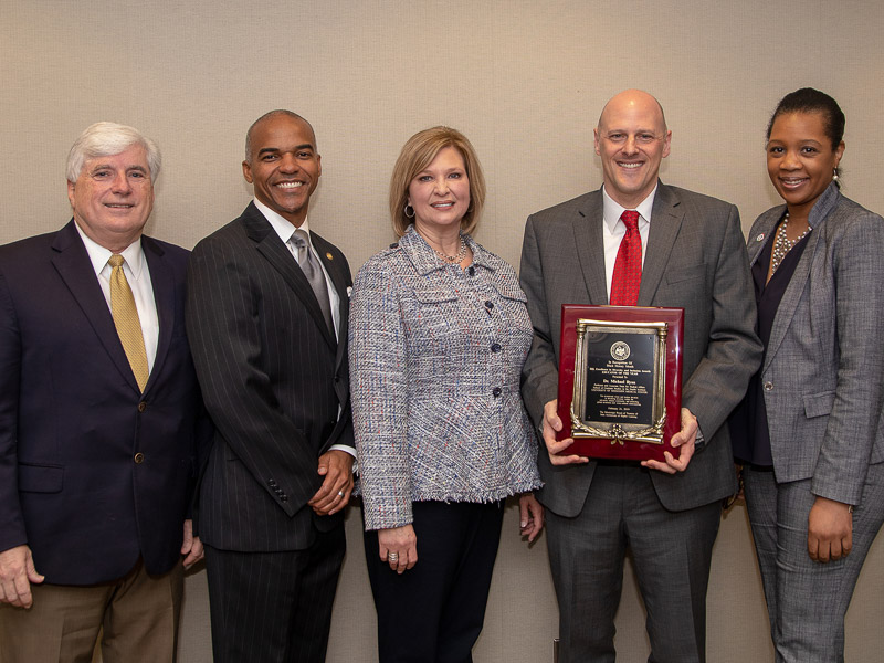 Dr. Mike Ryan holding his award posing with Dr. Joey Granger, UMMC dean of the School for Graduate Studies in the Health Sciences; Dr. Steven Cunningham, IHL board of trustees; Dr. LouAnn Woodward, UMMC vice chancellor; Dr. Juanyce Taylor, UMMC chief diversity and inclusion officer.