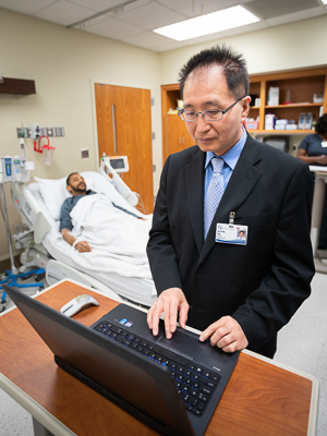 Doctor on computer with patient in the background