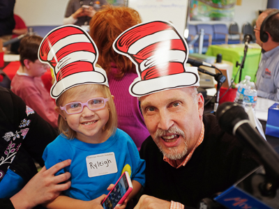 Ryleigh Sayers smiles with John Anthony of Mix 98.7 during a Mississippi Miracles Radiothon.