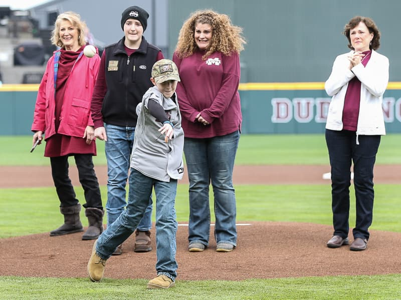 Flanked from his right by grandmother Karen Connerley; brother Caleb Connerley; mom Gena Connerley; and Gena's aunt, Cindy Christian, UMMC Grenada patient Corbin Connerley throws the first pitch Feb. 22 at a Mississippi State University home game. Photo courtesy of Kelly Donoho/ Mississippi State University Athletics