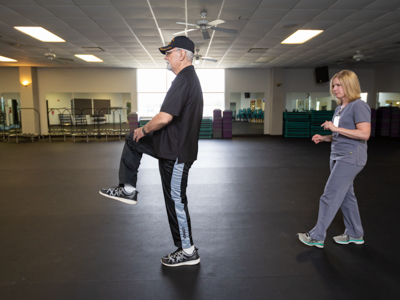 Richard Norton high-steps in an exercise to improve his balance while physical therapist Rachel Dear follows.