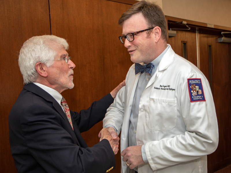 Dr. Lincoln Arceneaux, left, is congratulated by Dr. Brad Ingram, assistant professor of pediatric neurology, who paid tribute to his former professor during the room-naming ceremony Thursday.