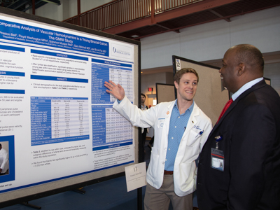 Preston Bell, a third-year medical student, discusses his project with mentor Dr. Ervin Fox, professor of medicine, at the annual Department of Medicine Research Day.