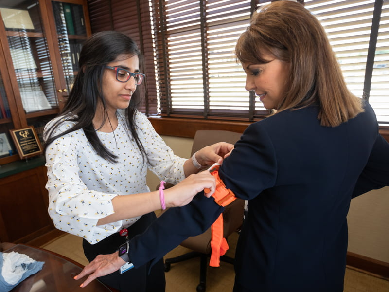 Harman Kaur, left, a third-year medical student, demonstrates the application of a standard tourniquet with assistance from Department of Surgery Manager of Business Operations Judy Gregory.