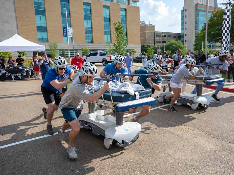 Tower Power of the MICU, left, and IV Pushers from Pharmacy head for the gurney races finish line.