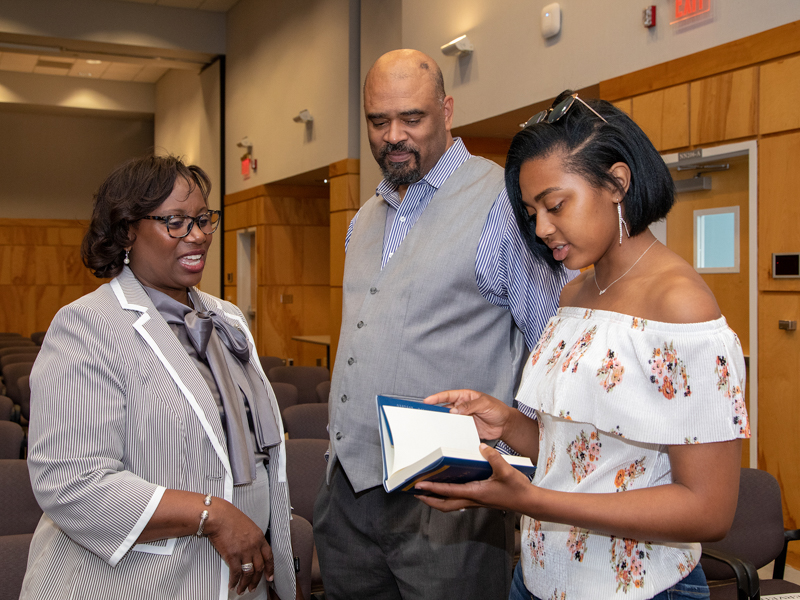 "Among those attending Dr. Loretta Jackson-Williams' address in the Student Union are her husband James Williams and their daughter Taylor, who's thumbing through a copy of Randy Pausch's ""The Last Lecture."""