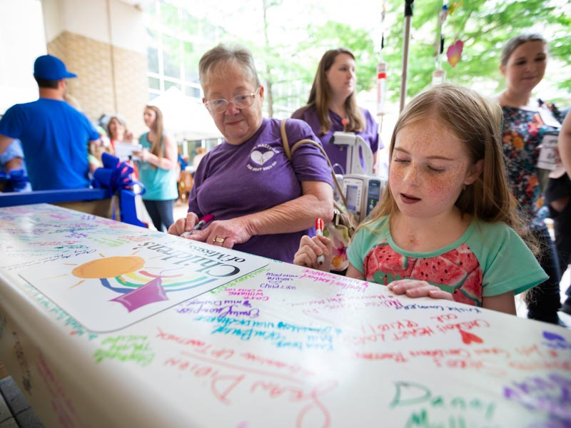 Sylvia Martin watches granddaughter Mackynlee Bedwell of Foxworth, a Batson patient, sign the beam that will be placed at the top of UMMC's pediatric expansion.