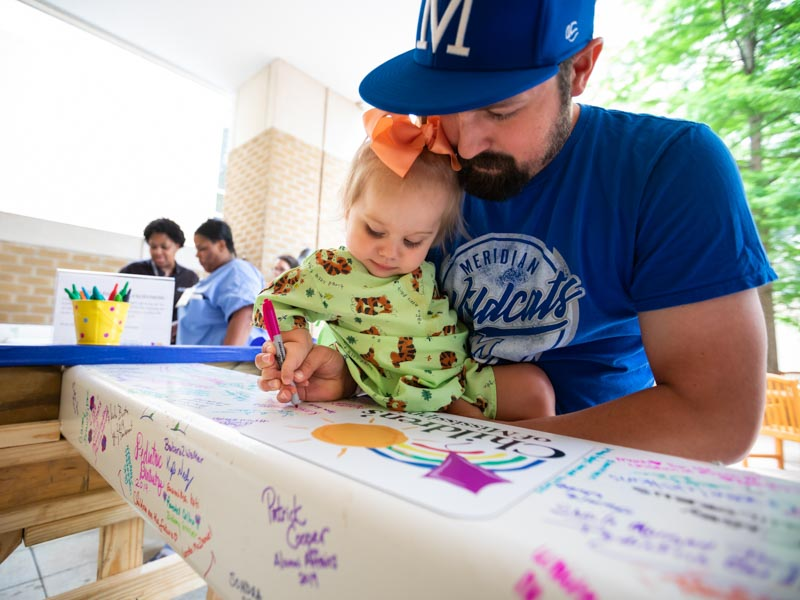 Jacob Drury of Philadelphia helps daughter Kinsley, a Batson patient, sign the beam.