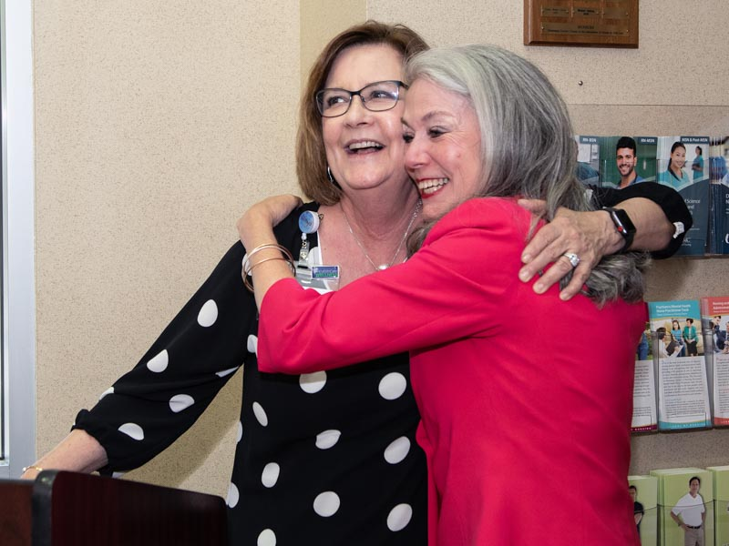 Terri Gillespie, left, chief nursing officer, receives a hug from Dr. Janet Harris after sharing stories about the former interim CEO at Harris' retirement celebration.