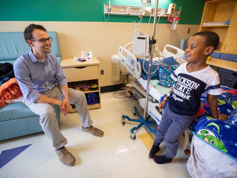 Alex Rueff, who served in the student chaplain position last year as a fourth-year medical student, shares a laugh with Princeton Donelson, Children's Hospital patient.