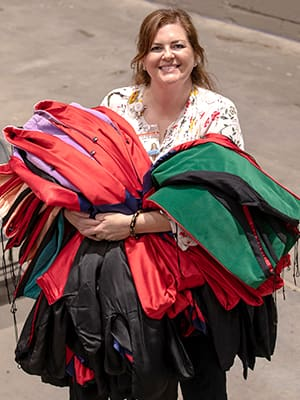 After UMMC's 2019 Commencement, Cole carries multicolored graduation robes away from another successful graduation ceremony at the Mississippi Coliseum.