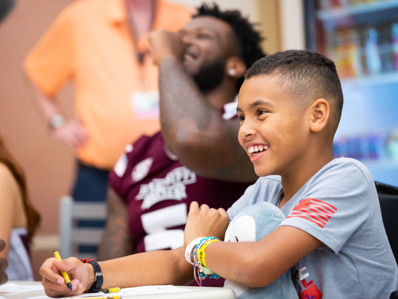Patient Johannon Payne of Pontotoc smiles while drawing pictures with the Mississippi State football team.