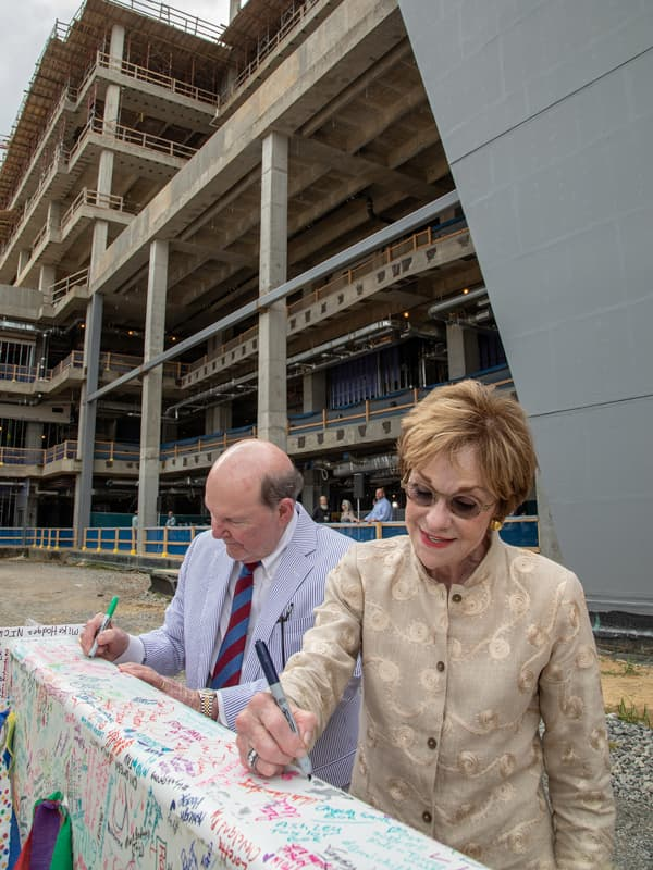 Campaign for Children's of Mississippi chairs Joe and Kathy Sanderson sign the beam before the topping-out ceremony for UMMC's pediatric expansion.