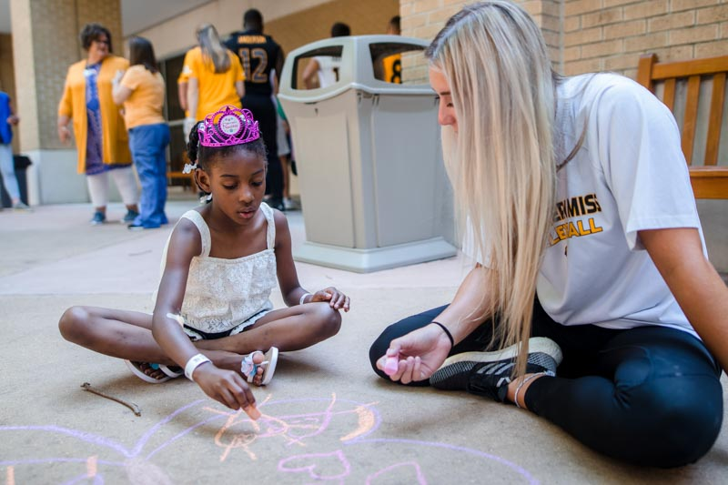 Southern Miss volleyball player Madison Lawler draws a sidewalk chalk mural with patient Zylee Oliver of Fayette.