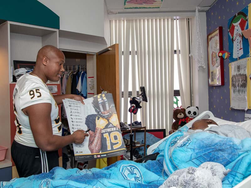 Southern Miss defensive lineman Andrew Cole delivers a Golden Eagles poster to Batson Children's Hospital patient Will Currie.