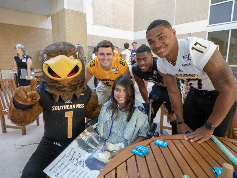 University of Southern Mississippi mascot Seymour and football players, from left, wide receiver Barrett Barham, wide receiver De'Michael Harris and quarterback Chandler Rogers smile with patient Imidrian York of Heidelberg.