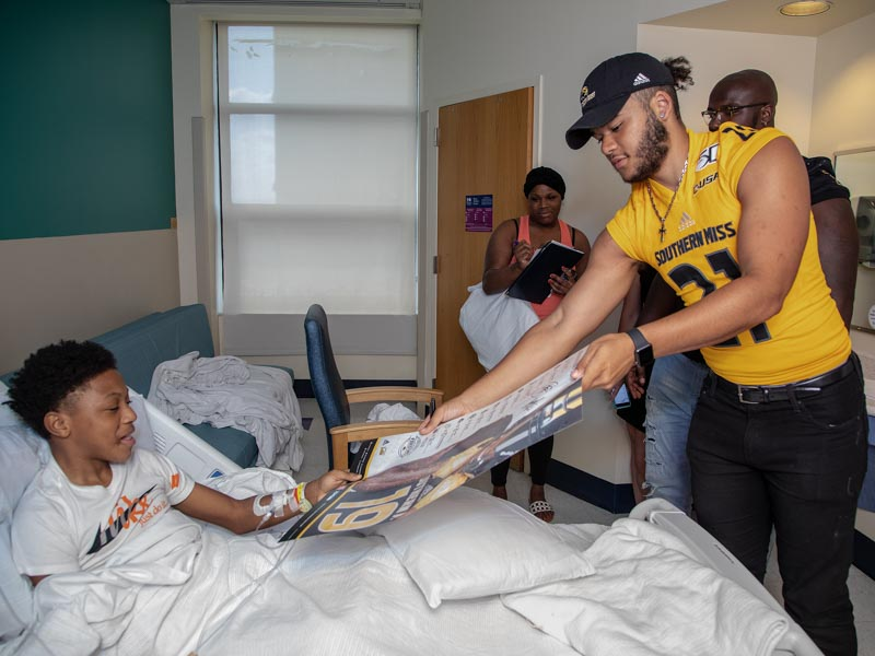 Southern Miss defensive back Rachuan Mitchell presents patient Quintarius Johnson of Bassfield with a signed Golden Eagles football poster.