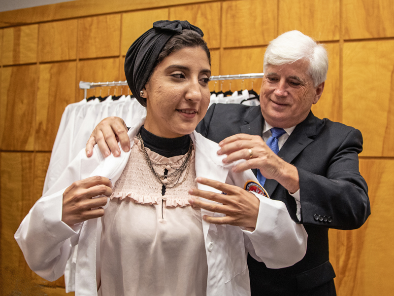 Incoming Ph.D. student Aya Ali receives her lab coat from Dr. Joey Granger at the School of Graduate Studies in the Health Sciences' White Coat Ceremony.
