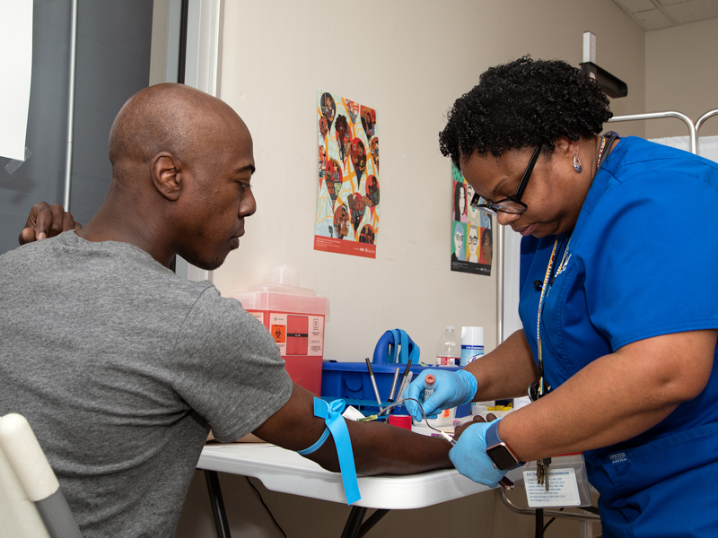 Sharron Vaughn, UMMC Biobank recruiter, draws blood from Travis Key of Jackson for the All of Us research study.