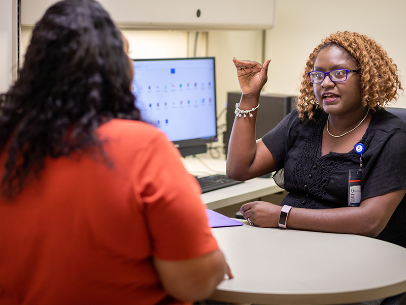 Benetra Mangum-Johnson, right, a social worker at UMMC's Adult Special Care Clinic, counsels Rosemary Hall.
