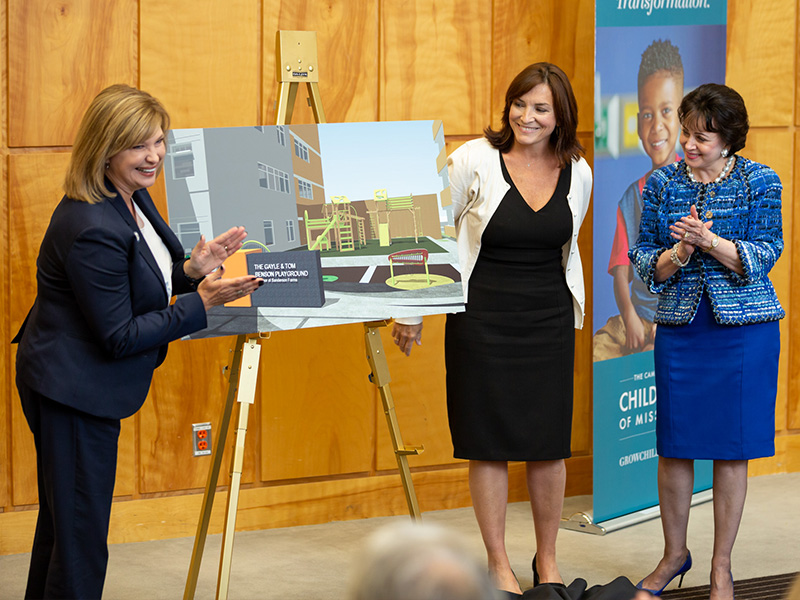 Dr. LouAnn Woodward, left, vice chancellor for health affairs and dean of the School of Medicine, applauds the $1 million gift from the Gayle & Tom Benson Charitable Foundation as Dr. Mary Taylor, Suzan B. Thames Chair, professor and chair of pediatrics, and Gayle Benson, right, owner of the New Orleans Saints and Pelicans, look on.