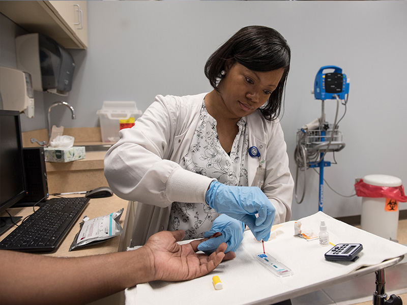 Jennifer Brumfield, a clinical research nurse, collects a blood sample for testing for HIV antibodies at UMMC's Express Personal Health Clinic.