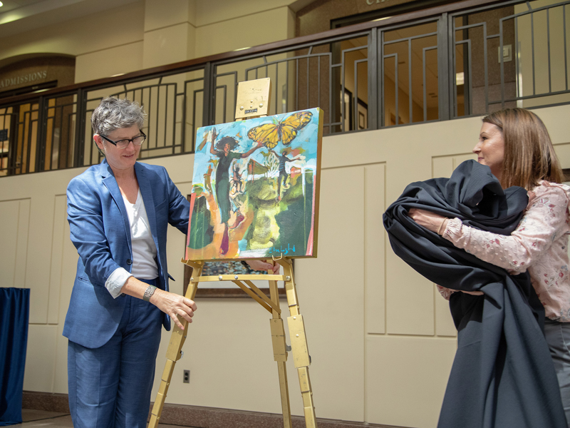 "Artist Ellen Langford, left, and Skye Stoker, director of UMMC's Office of Patient Experience, unveil Langford's painting, ""All of This,"" which celebrates Frances Anne Fortner's ""zest for life."""