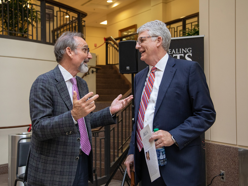 Malcolm White, left, executive director of the Mississippi Arts Commission, offers an impassioned critique of the proceedings to Tom Fortner, father of Frances Anne and UMMC's chief institutional advancement officer.