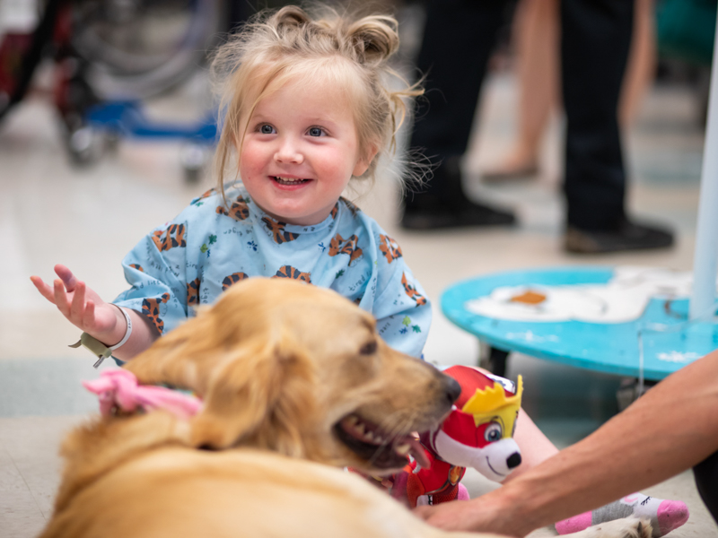 Children's of Mississippi patient Ruby Kate Greer of Hermanville smiles while visiting with Lady, a therapy dog.