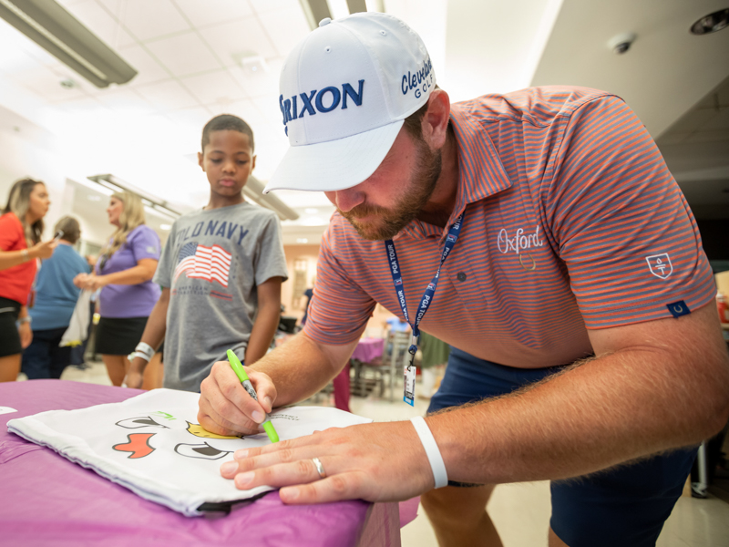 "Sanderson Farms Championship golfer Zach Sucher signs one of the tournament's ""chicken"" bags for Children's of Mississippi patient Mason Dantzler of Pearl."