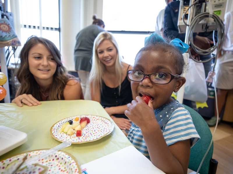 Children's of Mississippi patient Verlesia Mangum of Ridgeland eats a healthy snack during a visit from the PGA TOUR Wives Association.