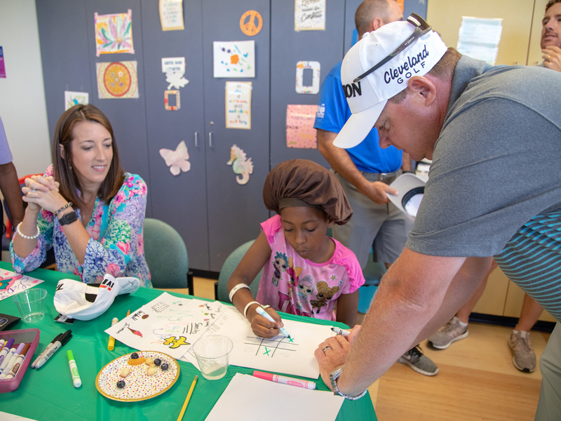 Cheri Potter and husband, Sanderson Farms Championship golfer Ted Potter Jr., play tic-tac-toe with Children's of Mississippi patient Mylaijah Simmons of Laurel.