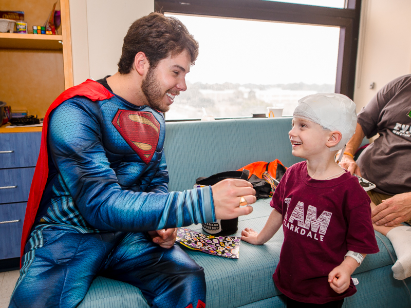 Children's of Mississippi patient Paxton Rogers of Pelahatchie gets Halloween stickers from Superman, aka PediaRebs member Gaston Box.