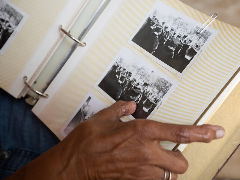 Sifting through one of her scrapbooks, Dr. Helen Barnes finds photos from her 1958 Howard University graduation day ceremony.