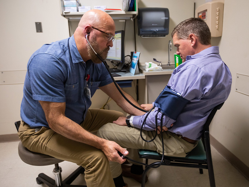 Jim Miller, left, TEAM Clinic nurse practitioner, takes Wes McComas's blood pressure.