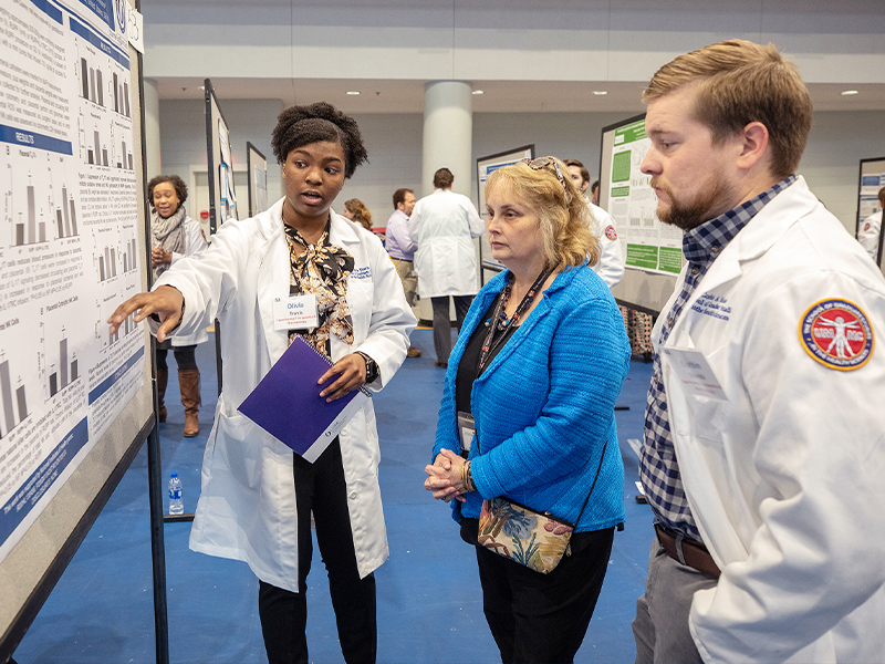 Dr. Barbara Alexander, center, the 2019 School of Graduate Studies in the Health Sciences Distinguished Alumna, talks to Ph.D. students Olivia Travis, and Corbin Shields during SGSHS Research Day.