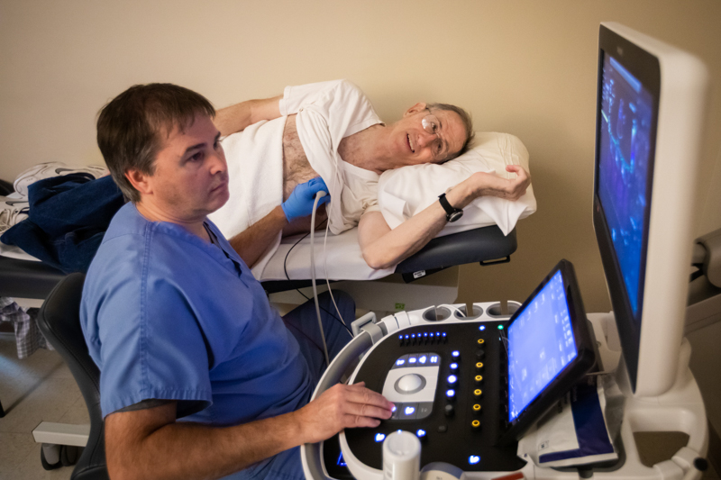 Karol Black, who conducts echocardiograms, works with Fred Robertson, cancer survivor, during a periodic screening at the UMMC Cancer Center and Research Institute.