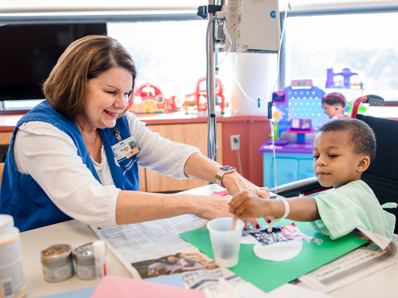 Begley helps Children's of Mississippi patient Joby Duck Jr. of Edwards glue tissue paper to his art project.