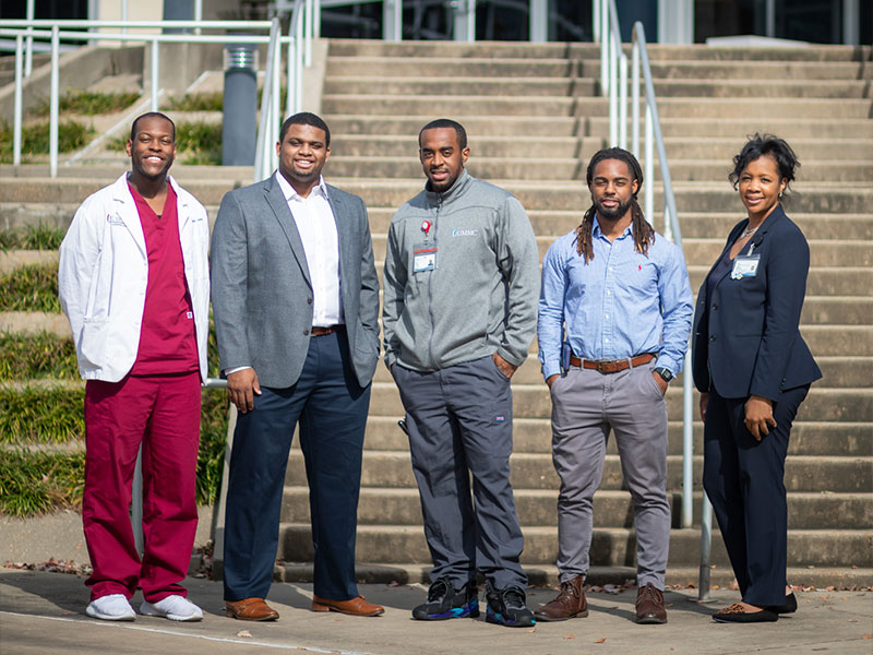 Former participants in the HELI program are still making their mark in health care at UMMC. Spending some time with their mentor, Dr. Juanyce Taylor, are, from left, Justin Johnson, a member of HELI's third cohort; Will Lindsey, a member of HELI's first cohort; Andre Funches, a member of HELI's first cohort; and Geoffrey Pratt, a member of HELI's third cohort.