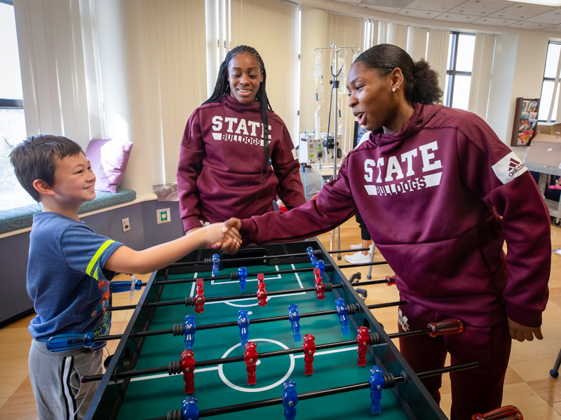 Women's basketball visits score wins with children's hospital patients