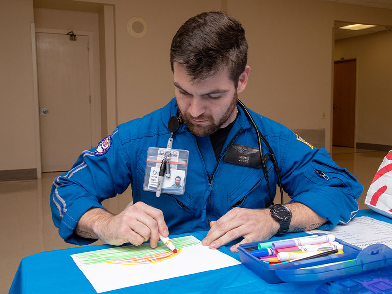 Air Care flight paramedic Cole Logan creates a sunrise that will be one of the thousands of drawings in the mural that will be on display in the lobby of the Children's of Mississippi expansion.