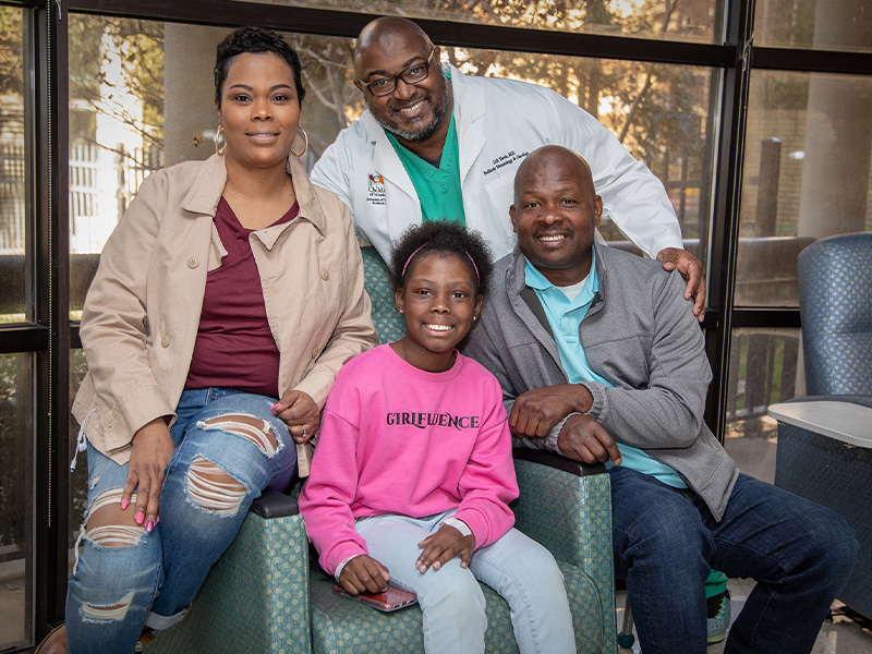 Kali Mitchell smiles with parents, Joneaset and Darold Mitchell, and hematologist/oncologist Dr. Dereck Davis.