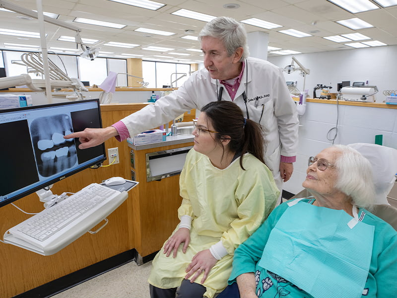 Dentist points at computer while dental student and patient look at the screen.