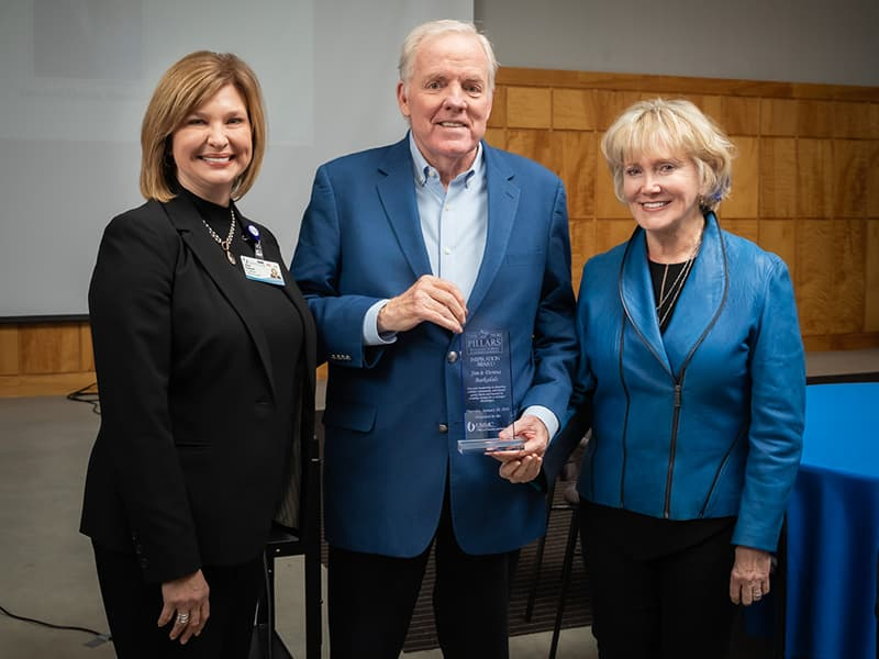 Dr. LouAnn Woodward, left, vice chancellor for health affairs, presented the Pillars Inspiration Award to Jim and Donna Barksdale.