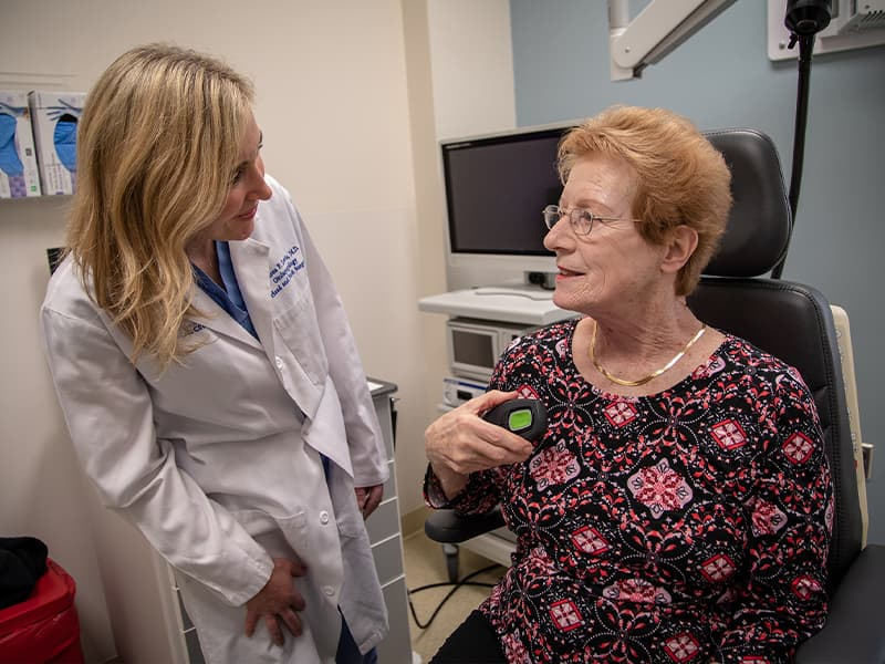 Doctor examines patient who is holding the device that helps open her airways for sleep.
