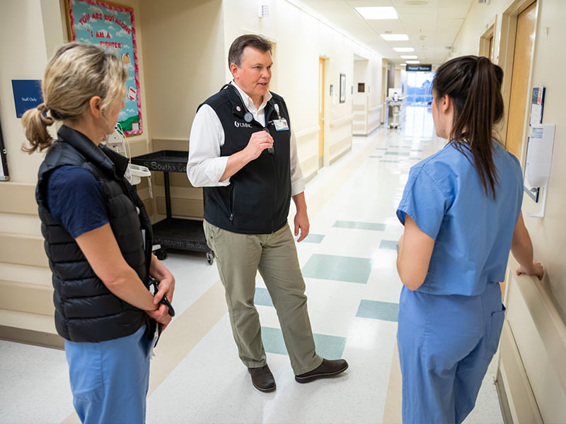 Doctor in hallway talks to two residents in scrubs.
